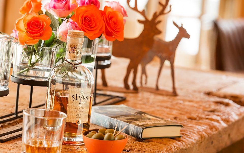 Single Malt Whisky mit Rosen und Dekoration im Hintergrund