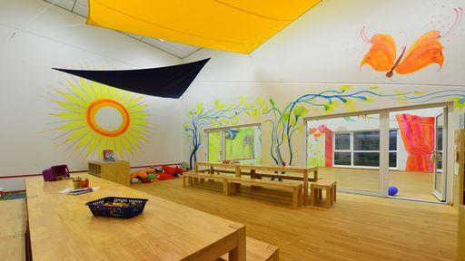 Indoor-Spielplatz bietet einen Turm mit drei Rutschen, eine Schaukelschlange und eine Elefanten-Wippe.