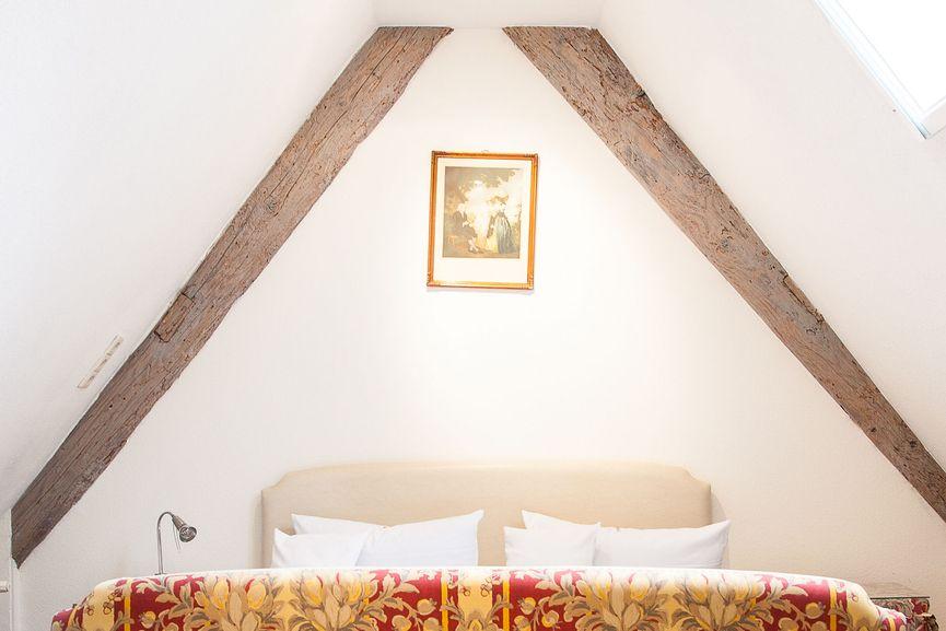Doppelbett unter der Dachgiebel im Hotel Zur Sonne